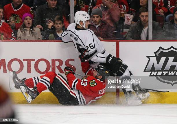 Slava Voynov of the Los Angeles Kings falls on top of Kris Versteeg of the Chicago Blackhawks at the United Center on December 15 2013 in Chicago...