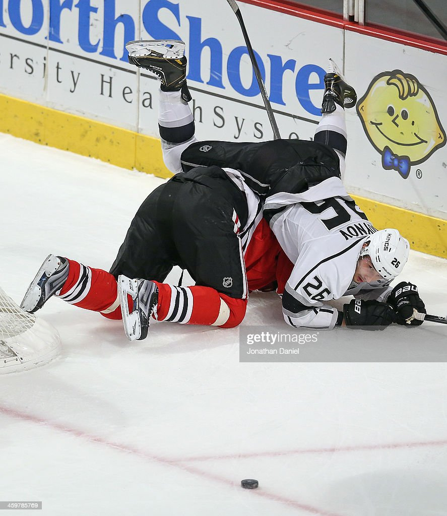 Slava Voynov of the Los Angeles Kings falls over Michal Handzus of the Chicago Blackhawks as the puck slips away at the United Center on December 30...