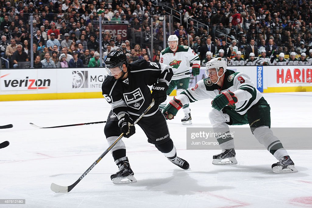 Slava Voynov of the Los Angeles Kings handles the puck while being pursued by Mikko Koivu of the Minnesota Wild at STAPLES Center on October 19 2014...