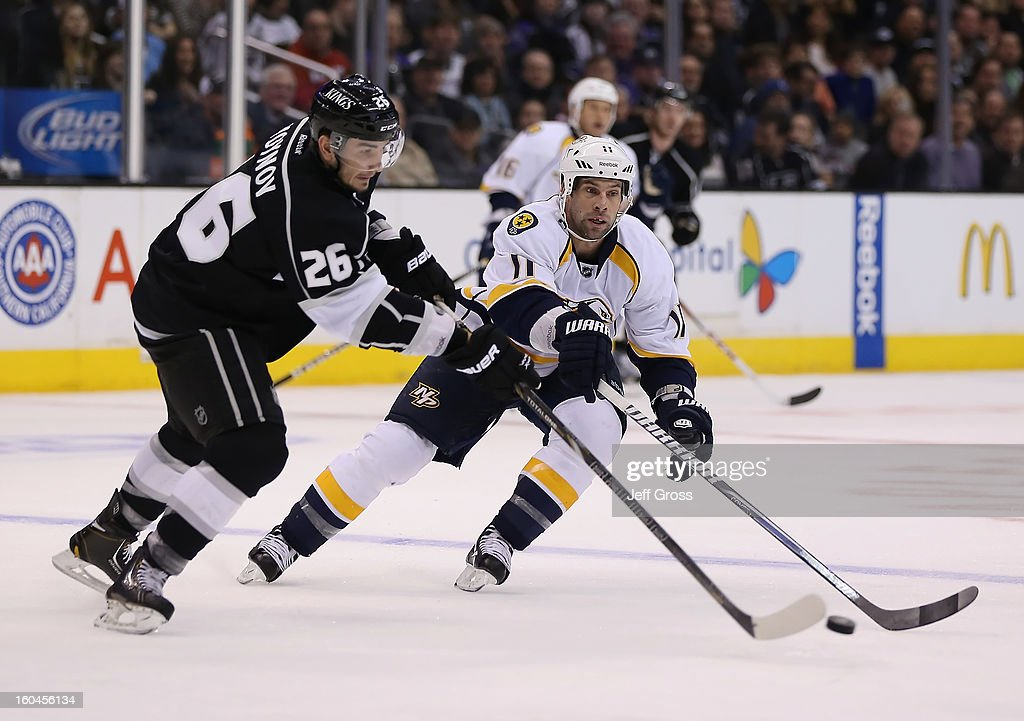 <a gi-track='captionPersonalityLinkClicked' href=/galleries/search?phrase=Slava+Voynov&family=editorial&specificpeople=8315719 ng-click='$event.stopPropagation()'>Slava Voynov</a> #26 of the Los Angeles Kings is pursued by <a gi-track='captionPersonalityLinkClicked' href=/galleries/search?phrase=David+Legwand&family=editorial&specificpeople=202553 ng-click='$event.stopPropagation()'>David Legwand</a> #11 of the Nashville Predators for the puck in the third period at Staples Center on January 31, 2013 in Los Angeles, California. The Predators defeated the Kings 2-1 in a shootout.