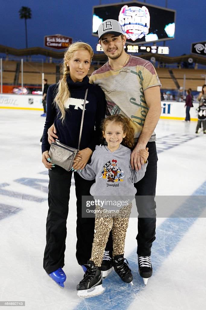 Slava Voynov of the Los Angeles Kings poses with his family during the family skate following team practice for the 2014 Coors Light NHL Stadium...