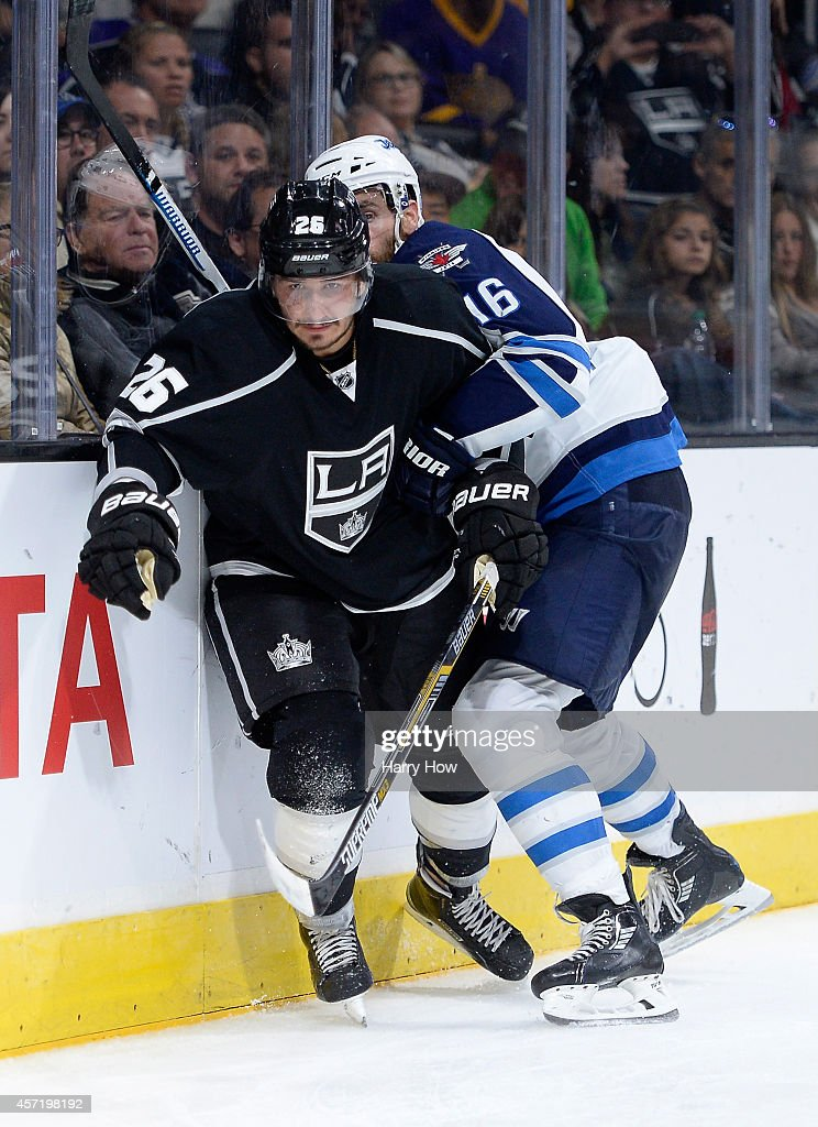 Slava Voynov #26 of the Los Angeles Kings skates from a check from Andrew Ladd #16 of the Winnipeg Jets during a 4-1 Kings win at Staples Center on October 12, 2014 in Los Angeles, California.