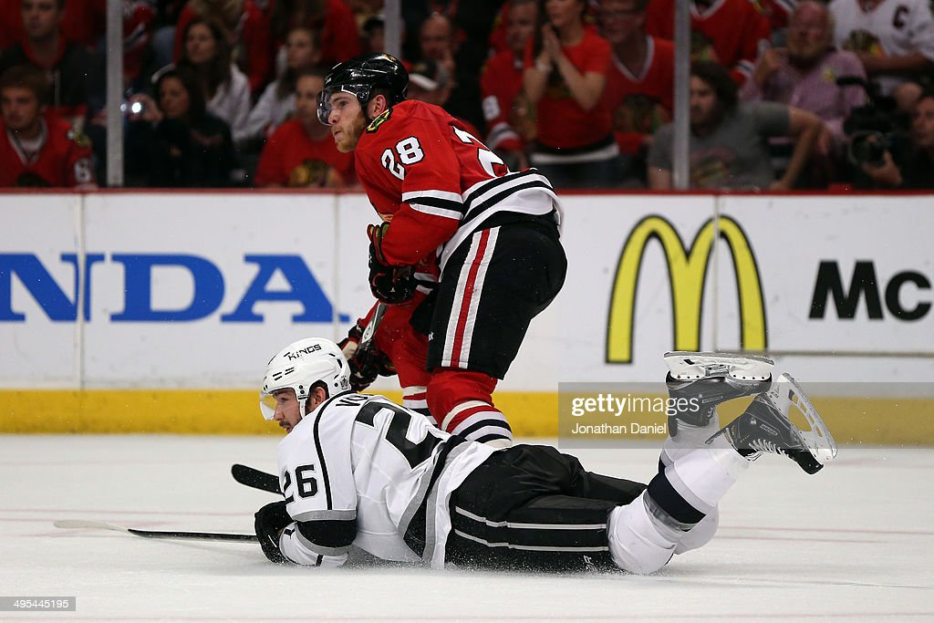 Slava Voynov #26 of the Los Angeles Kings slides on the ice against Ben Smith #28 of the Chicago Blackhawks during Game Seven of the Western Conference Final in the 2014 Stanley Cup Playoffs at United Center on June 1, 2014 in Chicago, Illinois.