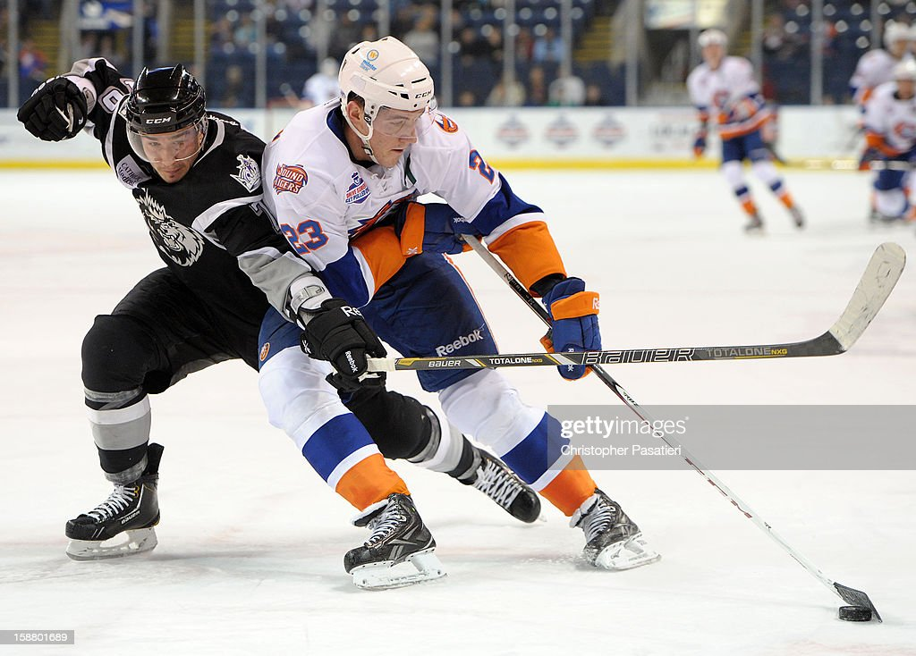 Slava Voynov #76 of the Manchester Monarchs gets his stick under John Persson #23 of the Bridgeport Sound Tigers during an American Hockey League game on December 29, 2012 at the Webster Bank Arena at Harbor Yard in Bridgeport, Connecticut.