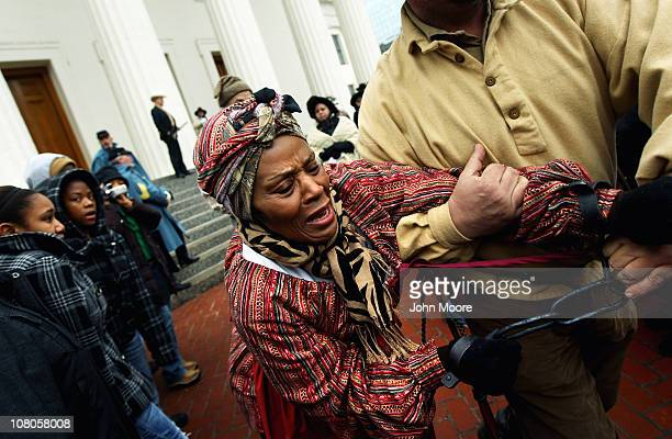 Slave reenactor Jannett White is led off in shackes after being 'auctioned' during a reenactment of a mid19th century slave auction January 15 2011...