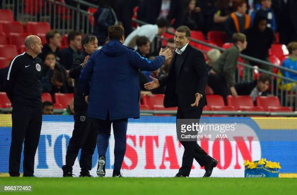 Slaven Bilic the head coach / manager of West Ham United shrugs his shoulders as he goes to shake the hand of Mauricio Pochettino manager / head...