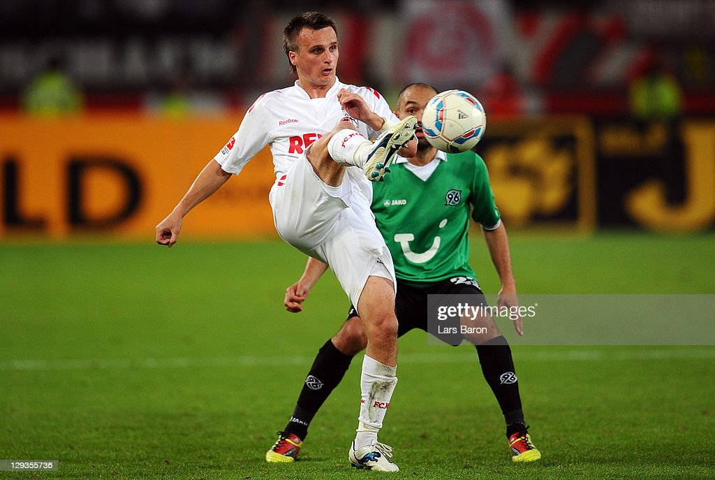 Slawomir Peszko of Koeln is challenged by Sofian Chahed of Hannover during the Bundesliga match between 1 FC Koeln and Hannover 96 at...