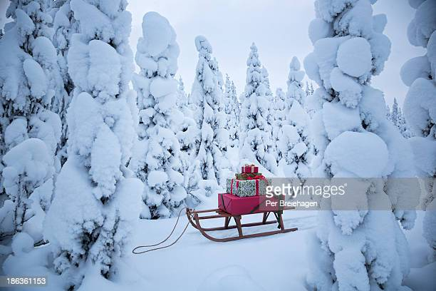 A sled with Christmas gifts in a snowy forest