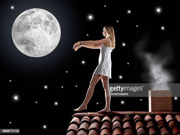 Sleep walker girl under the moon on roof top