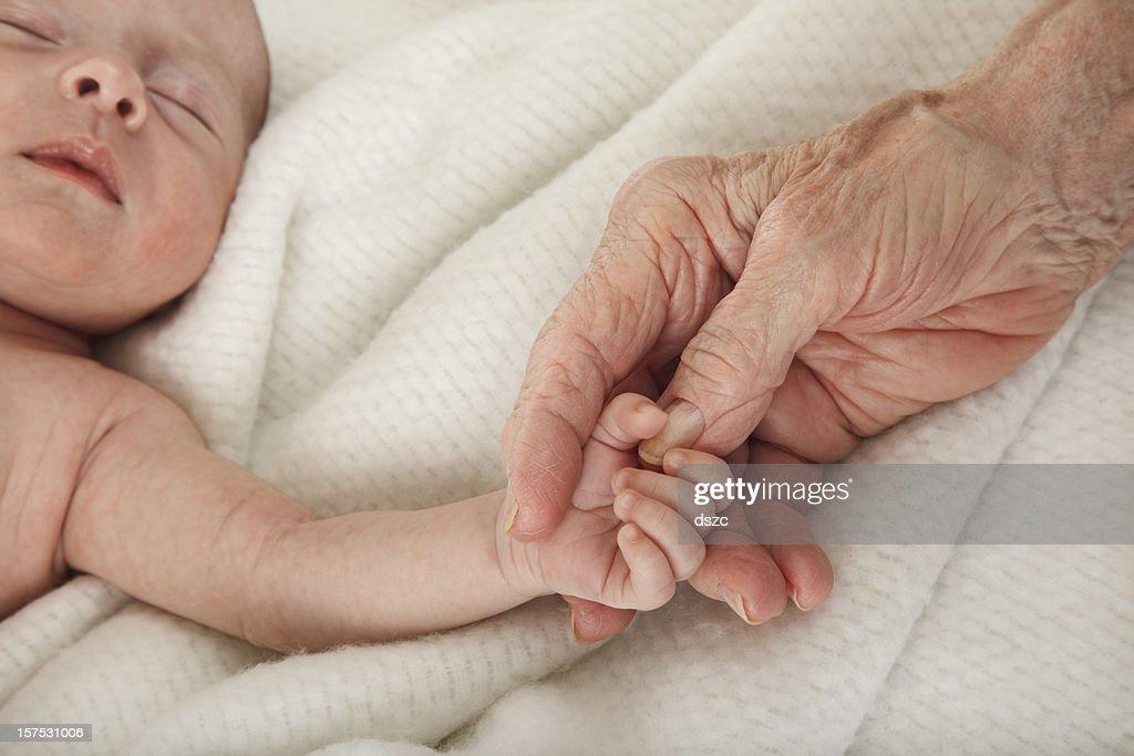 sleeping baby holding great grandmother's hand