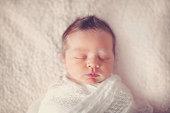 sleeping baby swaddled on white blanket