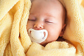 Frontal view of a cute baby girl with a soother in her mouth