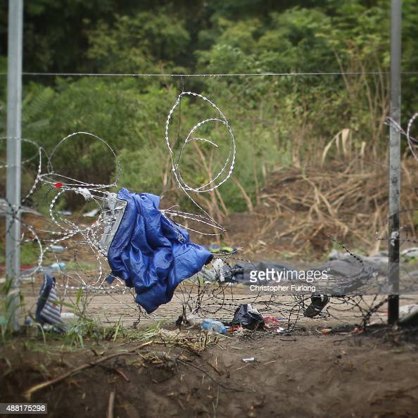 A sleeping bag and clothing hang from the razor wire as migrants discard items no longer wanted or needed when they cross the Hungarian border on...