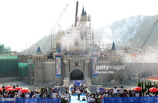 Sleeping Beauty Castle is topped with its final piece before a burst of colorful confetti fireworks music and Disney characters including Mickey...