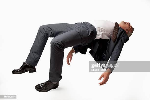 A sleeping businessman in mid-air, studio shot