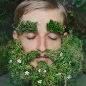 Sleeping hipster lying on grass with beard made of moss and flowers. Taking a nap in a fairytale old forest like a leprechaun, or dwarf concept