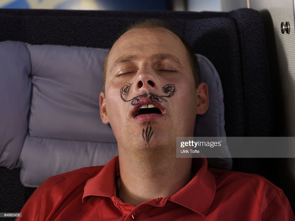 Sleeping man with drawn moustache : Stock Photo