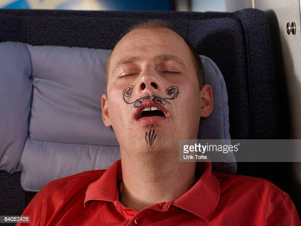 Sleeping man with drawn moustache