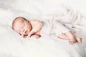 Sleeping newborn baby in a wrap on white blanket. Beautiful portrait of little child girl 7 days, one week old.