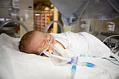 Sleeping newborn in hospital bed