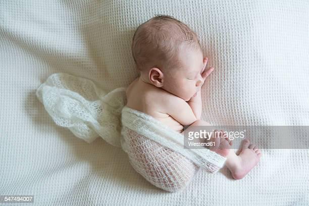 Sleeping newborn on white blanket