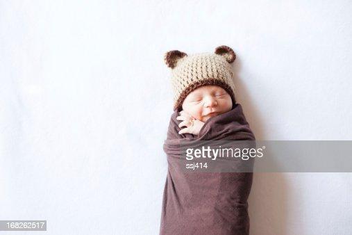 寝室新生児 Swaddled と帽子を着用ベア
