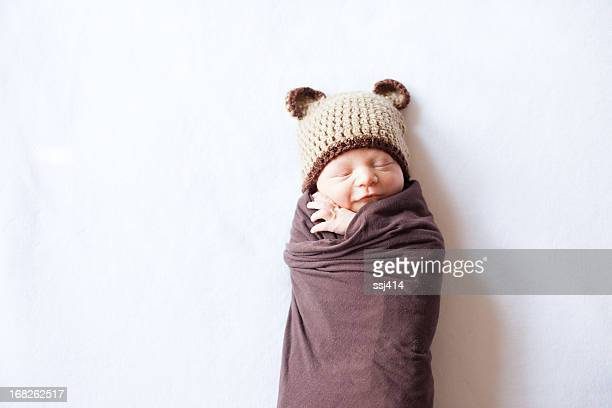 Sleeping Newborn Swaddled and Wearing a Bear Hat