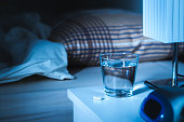 Sleeping pill on nightstand next to a glass of water. White tablet on table and bed in bedroom. Insomnia medicine concept.
