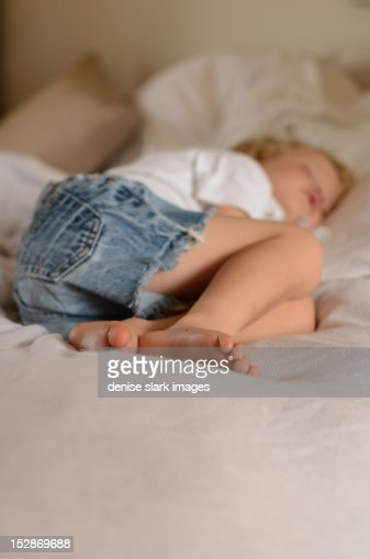 Sleeping young blond boy on bed : Stock Photo