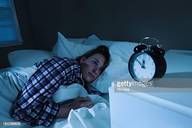 Jeune femme blanche avec des insomnies au lit, en regardant un radio-réveil avec connexion MP3