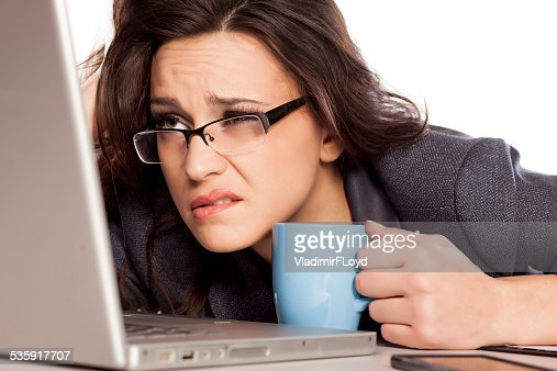 Sleepy and tired business woman on laptop, holding a coffee : Stock Photo