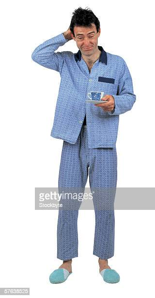 Sleepy man wearing pajamas holding a cup of tea