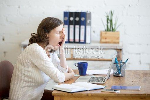 Sleepy young worker woman yawning : Stock Photo
