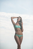 Slender beautiful girl in a swimsuit posing on the beach against the sea.