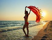 slender beautiful woman girl on beach with pareo shawl.