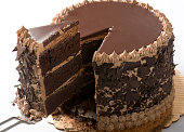 Chocolate cake being sliced in studio setting