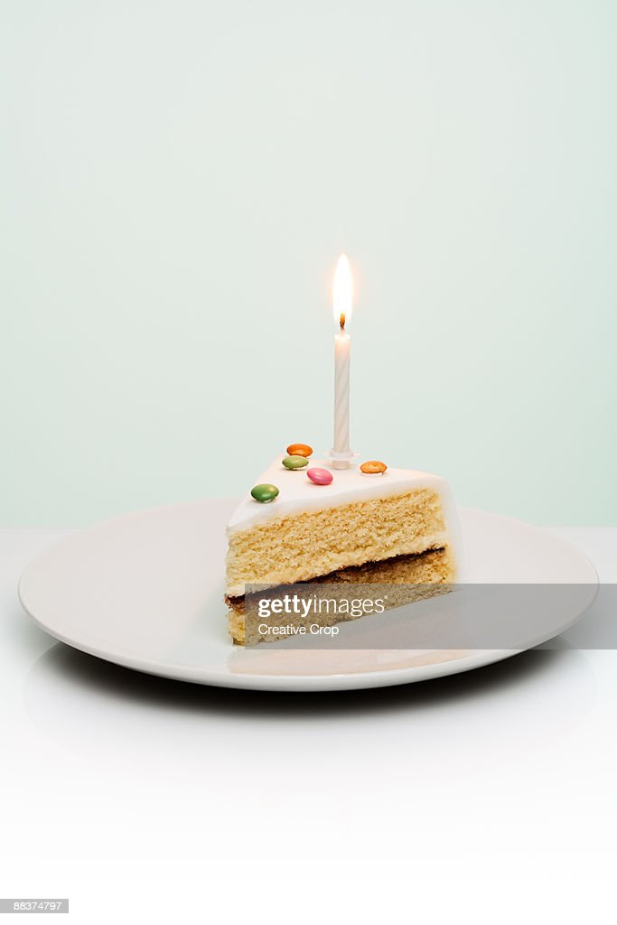 Slice of birthday cake with candle sticking out of