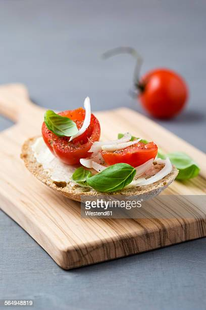 Slice of bread garnished with tomato, onion and basil leaves on wooden board