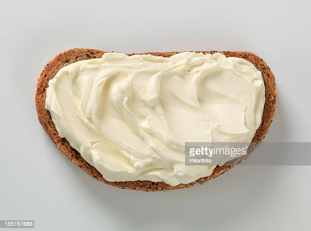 Slice of bread, spread with cheese against white background