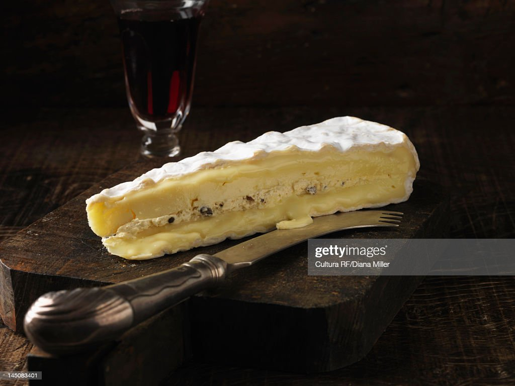 Slice of brie cheese on wooden board