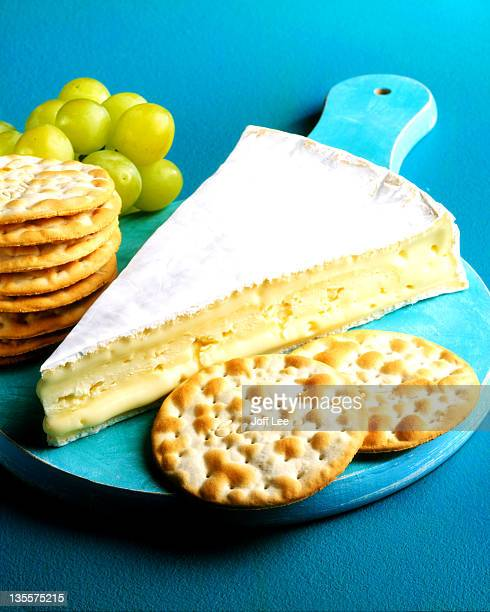 Slice of brie cheese with crackers & grapes