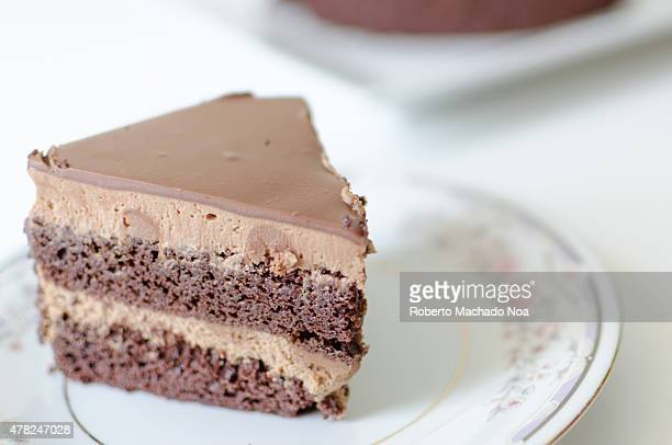 Slice of chocolate cake on a white plate on the table