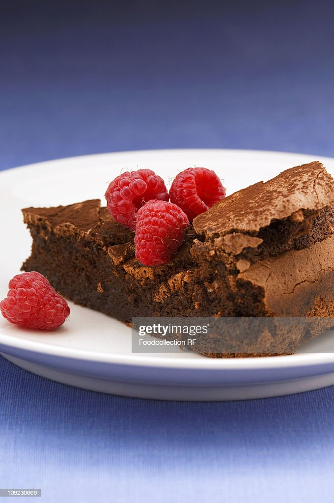 Slice of chocolate cake with raspberries on plate : Stock Photo