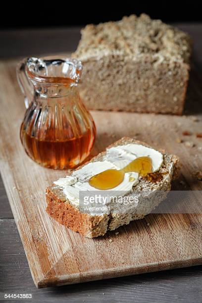 Slice of home-baked buckwheat bread with butter and honey on wooden board
