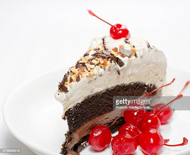 Slice of ice cream cake with cream nuts and cherry chocolate cake in a dish on white background macro