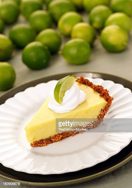 A slice of key lime pie surrounded by a pile of green limes