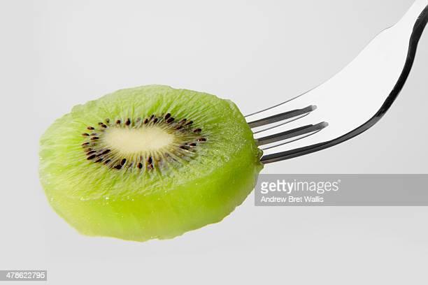 Slice of kiwi fruit on a fork