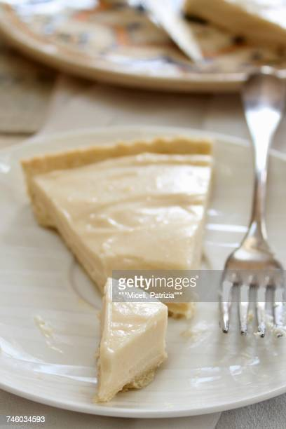 A slice of lemon cream tart on a plate with a fork