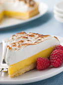 Slice Of Lemon Meringue Pie With Raspberries