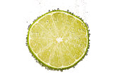 Slice of lime lemon in water with bubbles and clipping path